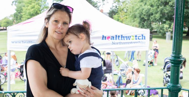 Mother holding her daughter on her hip at a Healthwatch event