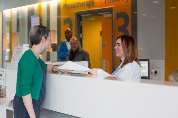 Woman speaking to someone at the hospital reception