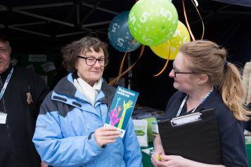 A Healthwatch volunteer holding a leaflet
