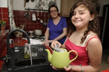 A young female carer helping her mum in the kitchen