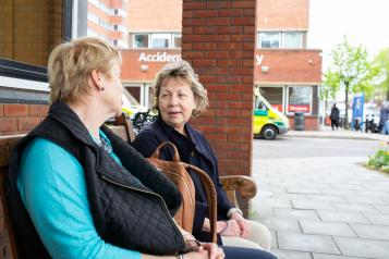 two women sitting outside hospital