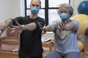 Man and elderly woman doing chair exercises