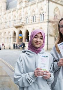 Two young teenagers holding up Healthwatch promotional material